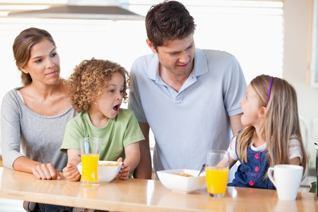 Family having breakfast in their kitchen photo
