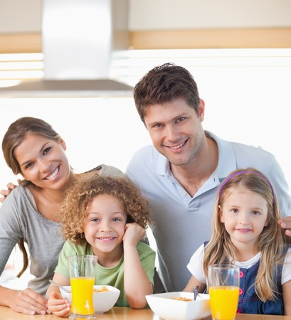 Smiling family having breakfast in their kitchen photo