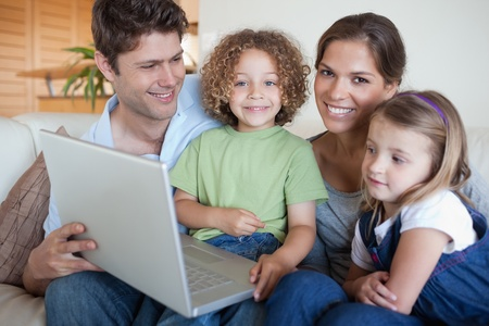 Smiling family using a laptop in their living room photo