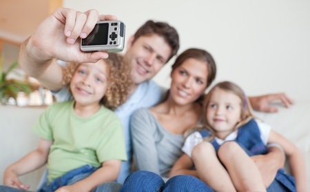 Happy family taking a photo of themselves in their living room photo