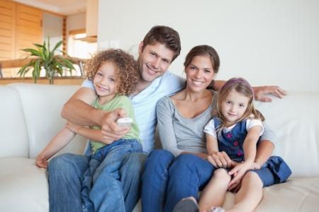 Glückliche Familie vor dem Fernseher zusammen in ihrem Wohnzimmer