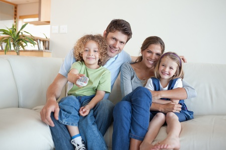 multiracial family: Smiling family watching TV together in their living room