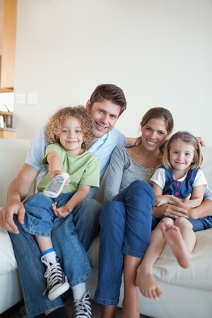 Portrait of a happy family watching TV together in their living room Stock Photo - 11682494