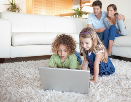 Children using a notebook while their parents are watching in their living room photo