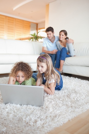 Portrait of children using a notebook while their parents are watching in their living room photo