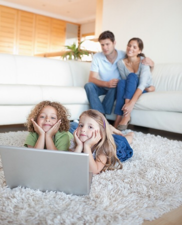 Portrait of cute children using a notebook while their parents are watching in their living room photo