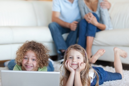 Cute children using a laptop while their parents are watching in their living room photo