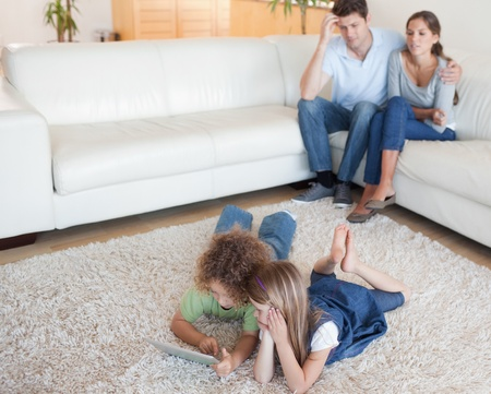 Cute children using a tablet computer while their parents are watching in their living room photo