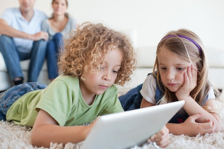 Serious children using a tablet computer while their happy parents are watching in their living room Stock Photo - 11681242