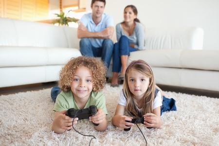 ni�os jugando videojuegos: Los ni�os que juegan juegos de video, mientras sus padres est�n viendo en su sala de estar