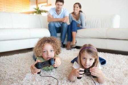 ni�os jugando videojuegos: Los ni�os lindos jugando a los videojuegos mientras sus padres est�n viendo en su sala de estar Foto de archivo