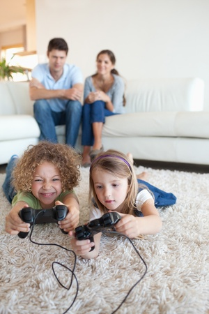 Portrait of children playing video games while their parents are watching in their living room photo