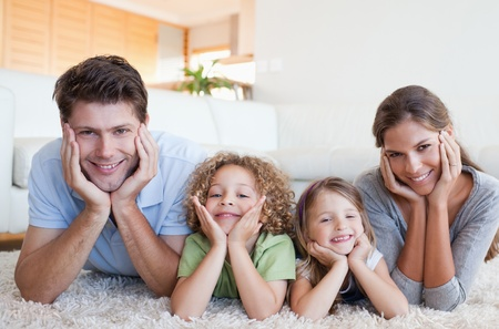 Family lying on a carpet in their living room photo