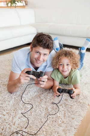 Portrait of a boy and his father playing video games while lying on a carpet photo