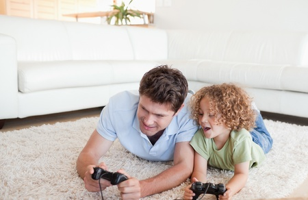 Cheerful boy and his father playing video games while lying on a carpet photo