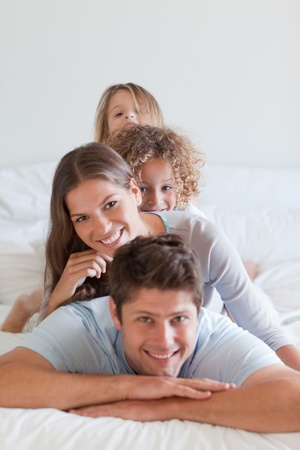 Portrait of a family lying on each other in a bedroom photo