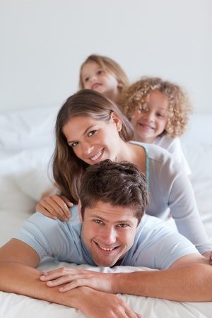 Portrait of a joyful family lying on each other in a bedroom photo
