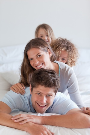 Portrait of a happy family lying on each other in a bedroom photo