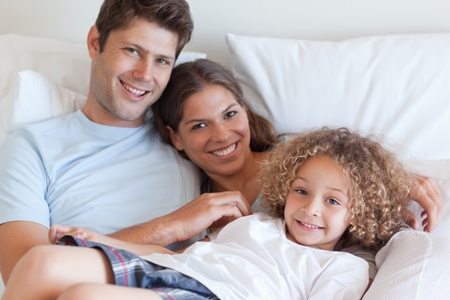 Smiling family relaxing on a bed while looking at the camera photo
