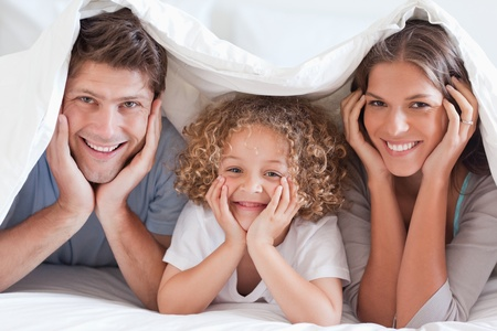 bedding indoors: Family posing under a duvet while looking at the camera