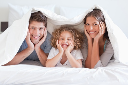 Happy family posing under a duvet while looking at the camera photo