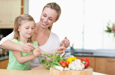 family support: Mother and daughter stirring salad together