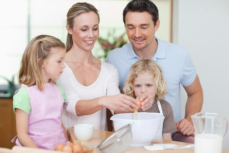 Happy family preparing dough together photo