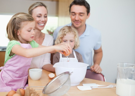 Happy smiling family preparing dough together photo