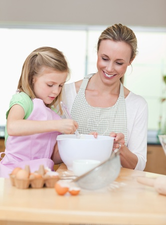 Smiling mother and daughter preparing dough for cookies togehter photo