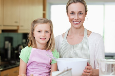 Mother and daughter together with bowl in the kitchen photo