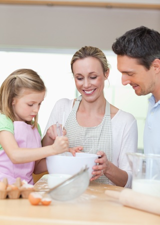 Smiling family preparing cookies together photo