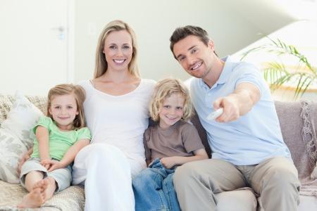 mujer viendo tv: Familia viendo la televisi�n juntos en el sof� Foto de archivo