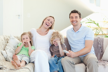 Family laughing on the sofa together photo