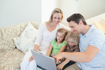 Family together on the couch with laptop