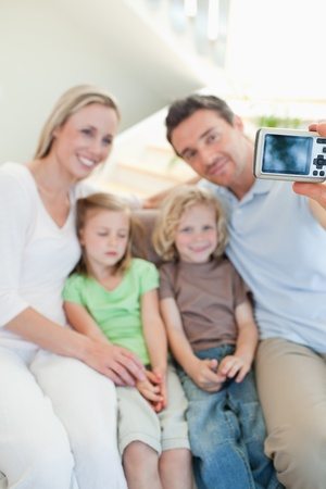 Man taking family picture on the sofa photo