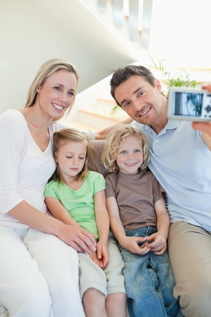 Man taking family picture on the couch photo