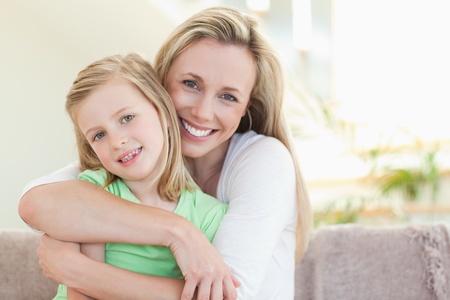 afecto: Madre abrazando a su hija en el sof�