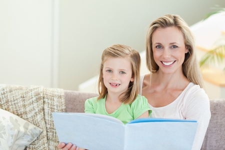 Mutter und Tochter in einer Zeitschrift zusammen auf dem Sofa Lizenzfreie Bilder