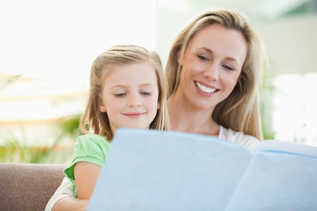 Mother and daughter reading a magazine together on the couch Stock Photo - 11686224