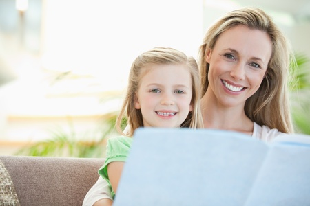 Mother and daughter reading together on the sofa Stock Photo - 11686017