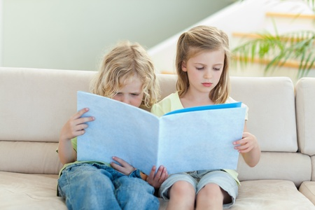 Siblings reading magazine together on the sofa photo