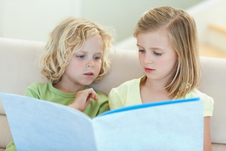 Siblings reading magazine together on the couch photo