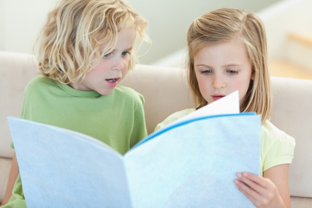 Siblings on the sofa reading magazine together photo