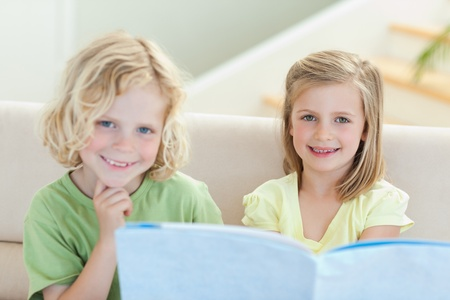 Siblings on the couch reading magazine together photo
