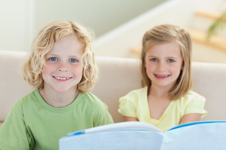 Siblings reading booklet together on the sofa photo