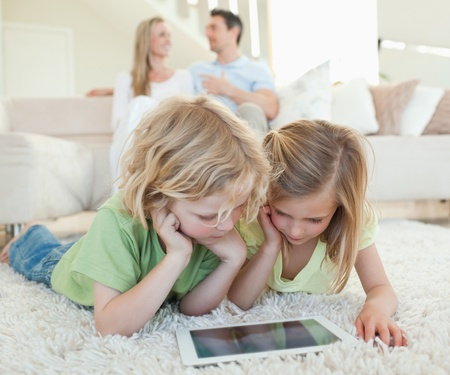computer games: Children on the floor together with tablet and parents behind them Stock Photo