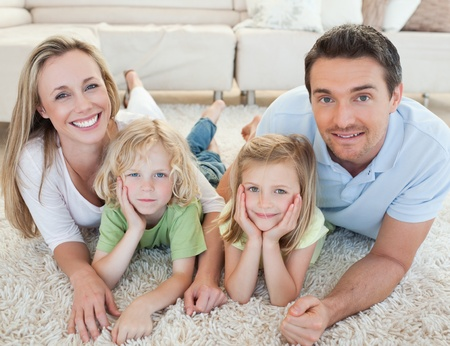 Family lying on the carpet together photo