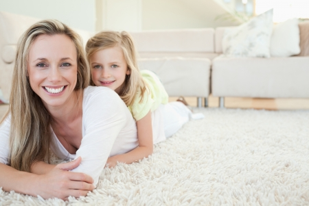 family in living room: Mother and daughter lying on the floor together