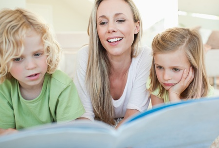 Mother reading magazine together with her children photo