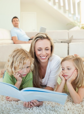 Mother reading magazine together with her children on the floor Stock Photo - 11686036